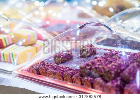 Traditional Turkish Delight Rahat Lokum and Other Oriental Sweets in Market. Traditional Purple Turkish Delight Rose Leaves Lokum Candy. poster