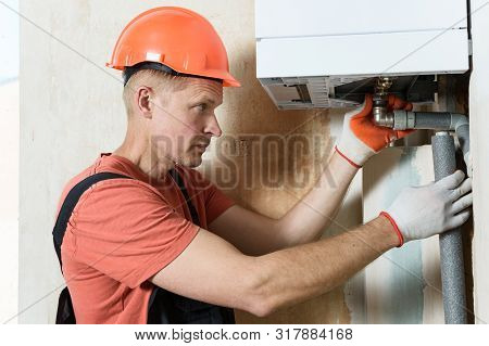 The Worker Is Connecting The Pipes To A Domestic Gas Boiler.