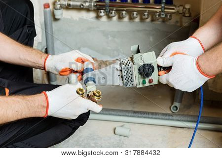 The Worker Is Soldering Plastic Pipes With H-piece Valve For Home Heating System.