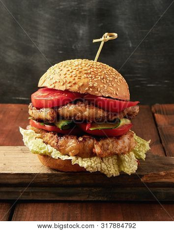 Hamburger With Pork Fried Steak, Red Tomatoes, Fresh Round Bun With Sesame Seeds On A Vintage Brown