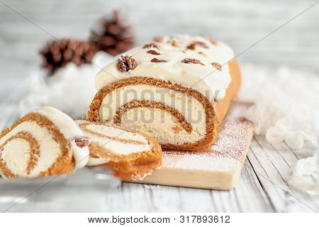 Beautiful Fresh Baked Pumpkin Spice Roll Cake With Powdered Sugar, Pecans, Cream Cheese Filling And