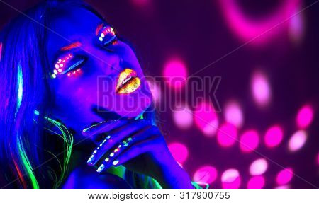 Neon Woman dancing. Fashion model woman in neon light, portrait of beautiful model with fluorescent make-up, Art design of female disco dancer posing in UV, colorful make up. On bright background