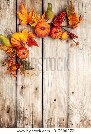 Festive autumn decor from pumpkins, berries and leaves on a rustic wooden background. Concept of Thanksgiving day or Halloween. Flat lay autumn composition with copy space.