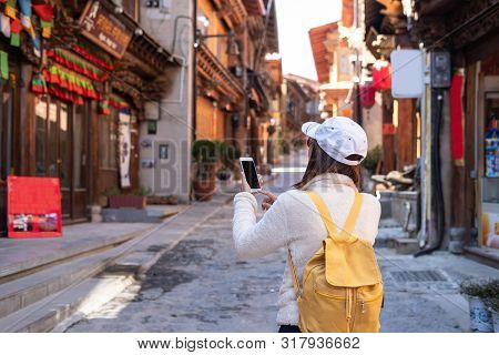 Young Woman Traveler Walking In The Old Town, Shangri-la And Using Smartphone For Searching Location