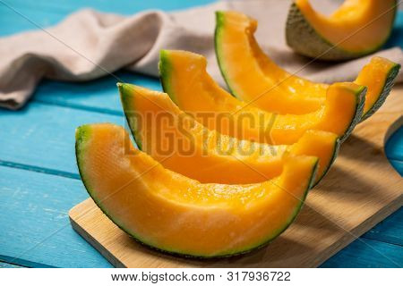Close Up Of Sliced Ripe Melon On Wooden Table