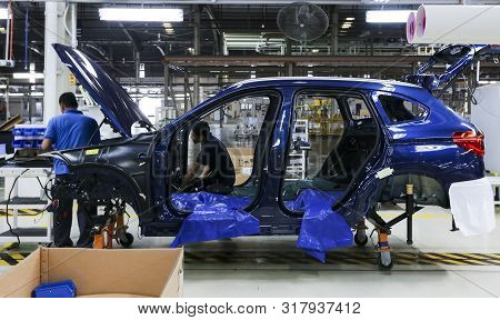Workers Assembles Cars At Automobile Assembly Line Production Plant