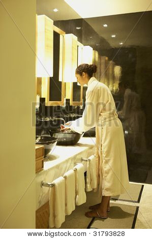 Woman washing her hands in spa bathroom