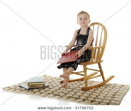 An adorable preschooler looking satisfied after reading a good book.  On a white background.