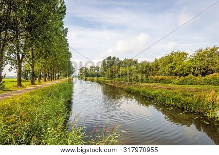 Long And Straight Canal In A Rural Landscape In The The Dutch Summer Season. Along The Canal Is A Ro
