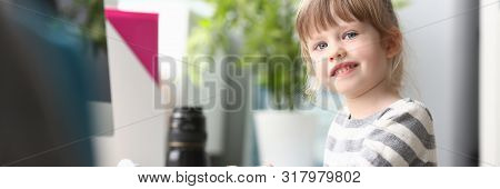 Cute Little Girl Sitting At Home At Worktable Looking In Camera Portrait