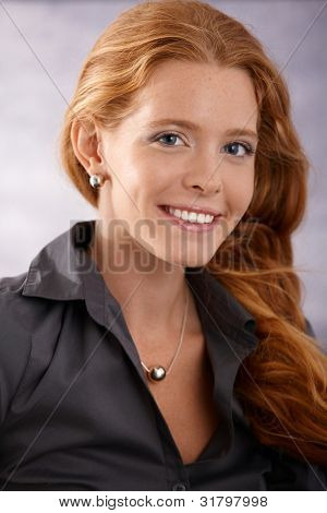 Closeup portrait of beautiful elegant woman with long red curly hair smiling at camera happily.
