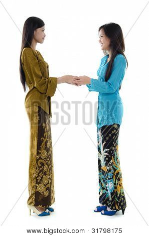 Portrait of Malay girls with kebaya greeting on white background