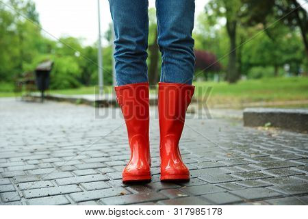 Woman With Rubber Boots In Puddle, Closeup. Rainy Weather
