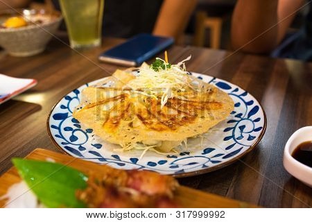 Deep Fried Gyoza Or Jiaozi On Plate On Wooden Table In Japanese Restaurant.