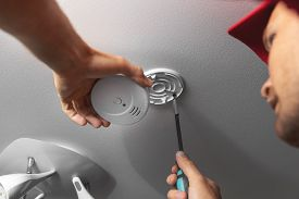 Handyman Installing Smoke Detector On Ceiling At Home