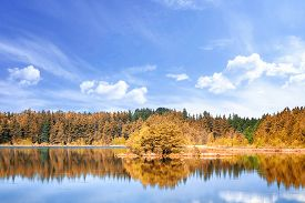 Autumn Lake Scenery With Colorful Trees Under A Blue Sky In The Summer