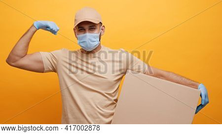 Strong Young Courier With Face Mask Flexing Muscle While Holiding Cardboard Box. High Quality Photo