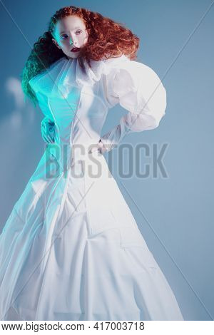 Sophisticated female model with lush red curly hair posing in a white art dress. A studio portrait with mixed red color lighting. Fashion art.