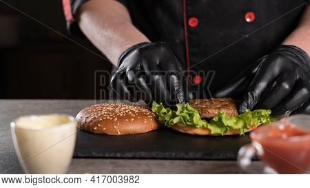 Step By Step Recipe. Stage 4. The Chef Prepares A Delicious Burger. Close-up Of A Hand In Black Glov