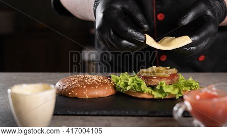 Step By Step Recipe. Stage 7. The Chef Prepares A Delicious Burger. Close-up Of A Hand In Black Glov