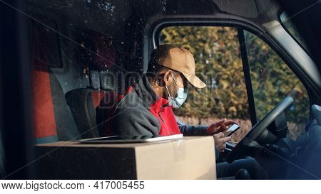 Courier Getting In Touch With Client Using Smartphone On Drivers Seat. Man With Face Mask Delivering
