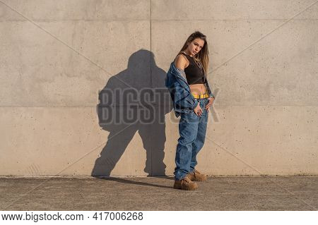 Nice Young Woman Dressed In Casual Clothes With Shadow Reflected On The Wall