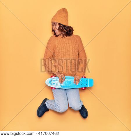 Young beautiful latin skater woman smiling happy. Jumping with smile on face holding skate over isolated yellow background