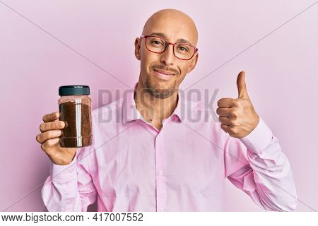 Bald man with beard holding soluble coffee smiling happy and positive, thumb up doing excellent and approval sign