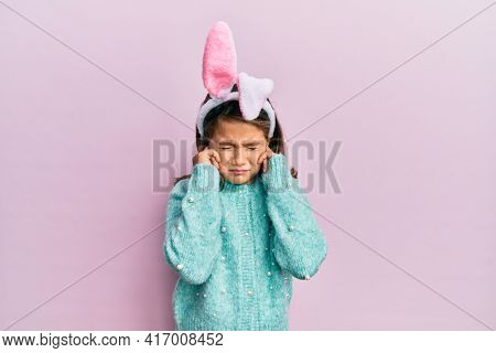 Little beautiful girl wearing cute easter bunny ears covering ears with fingers with annoyed expression for the noise of loud music. deaf concept.