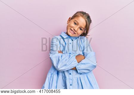 Little beautiful girl wearing casual clothes happy face smiling with crossed arms looking at the camera. positive person.