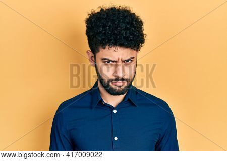 Young arab man with beard wearing casual shirt skeptic and nervous, frowning upset because of problem. negative person.