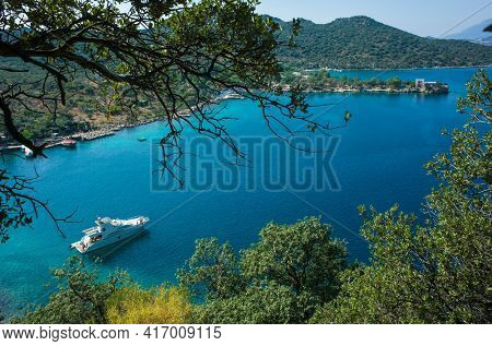 White boat anchored in picturesque bay near Kas, Mediterranean sea coast, Nature of Turkey, View from Lycian way hiking trail, black tree branches in foreground