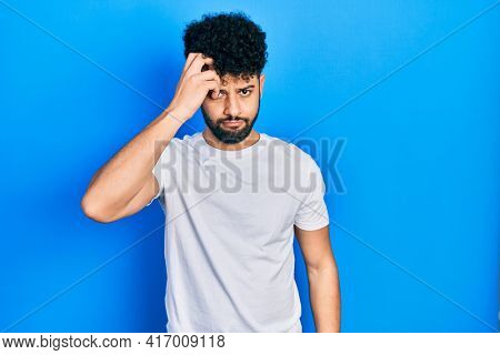 Young arab man with beard wearing casual white t shirt worried and stressed about a problem with hand on forehead, nervous and anxious for crisis