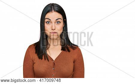 Young hispanic woman wearing casual clothes puffing cheeks with funny face. mouth inflated with air, crazy expression.