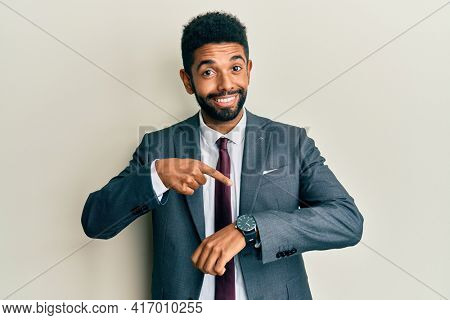 Handsome hispanic man with beard wearing business suit and tie in hurry pointing to watch time, impatience, upset and angry for deadline delay