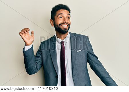 Handsome hispanic man with beard wearing business suit and tie dancing happy and cheerful, smiling moving casual and confident listening to music