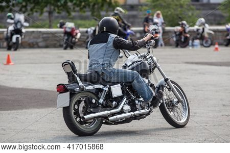 Motorcyclist Rides A Motorcycle On A Background Of Parked Motorcycles