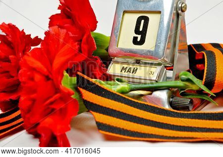 9 May background, Victory day concept, 9 May card, 9 May backgorund, 9 May design, vintage metal desk calendar with 9th May date and George ribbon and red carnations - 9 May Victory Day concept