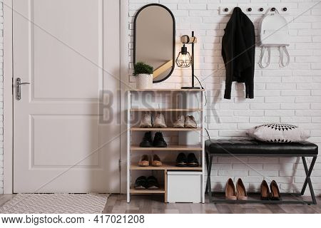 Shelving Unit With Shoes And Different Accessories Near White Brick Wall In Hall. Storage Idea