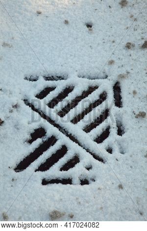 An Access Grate Cover Partly Covered In Snow