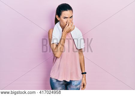 Young brunette woman wearing sportswear and towel smelling something stinky and disgusting, intolerable smell, holding breath with fingers on nose. bad smell