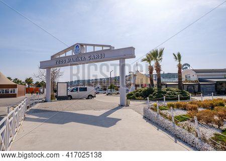 Seferihisar, Izmir, Turkey - 03.08.2021: Teos Marina Town Center With An Arch. Translation On It: Te