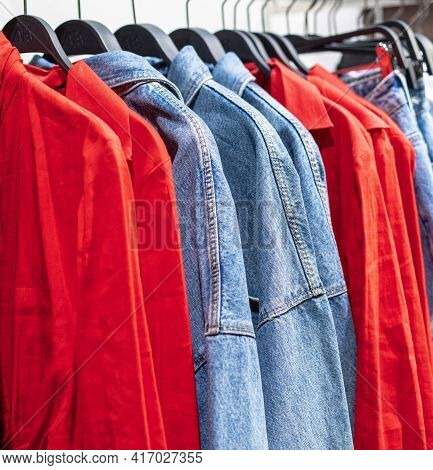 Hangers With Comfortable Denim Clothing In The Chain Store. Blue Denim Shirts And Jackets, Red Loose