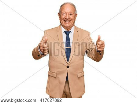 Senior caucasian man wearing business suit and tie approving doing positive gesture with hand, thumbs up smiling and happy for success. winner gesture.