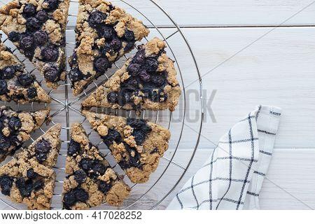 Freshly Baked Oat Blueberry Scones On Cooling Rack On White Wooden Background. High Angle View. Vega