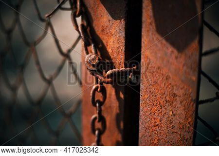 An Old Rusty Gate With A Mesh Fence Is Closed On A Rusty Chain, Illuminated By Light. An Abandoned P