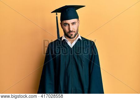 Young hispanic man wearing graduation cap and ceremony robe skeptic and nervous, frowning upset because of problem. negative person.