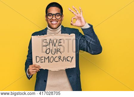 Young handsome hispanic man holding save our democracy protest banner doing ok sign with fingers, smiling friendly gesturing excellent symbol