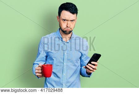 Hispanic man with beard using smartphone and drinking a cup of coffee puffing cheeks with funny face. mouth inflated with air, catching air.