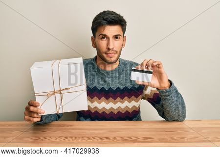 Young handsome man holding gift and credit card skeptic and nervous, frowning upset because of problem. negative person.